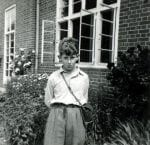 Black and white photograph of Adam Hart-Davis outside a classroom at St Andrew's School.