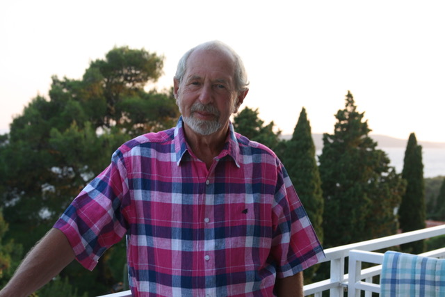 A designer committed to his craft, Bernard Higton takes a rare break, relaxing on the balcony of a holiday apartment. In this colour photograph he wears a red, white and blue check shirt.