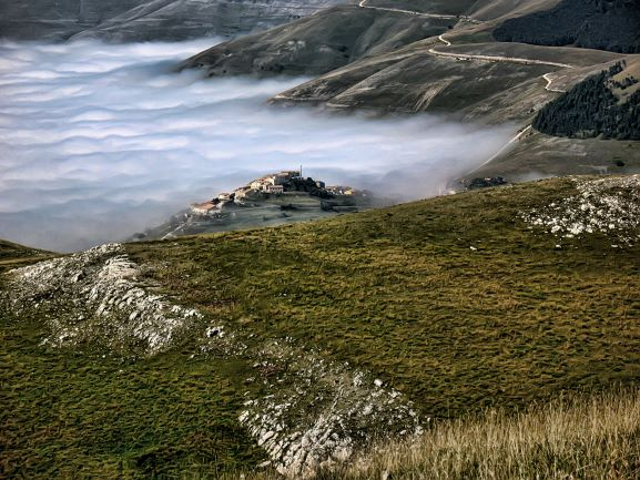 A photograph taken from a grassy mountaintop in the Marche reveals a mist-filled valley and the remote village of Castellúccio.