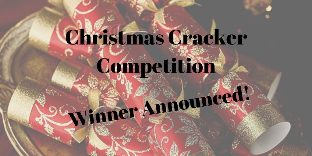 Photograph of red and gold crackers in the background, overlaid with black text announcing the winner of the Christmas Cracker Competition.