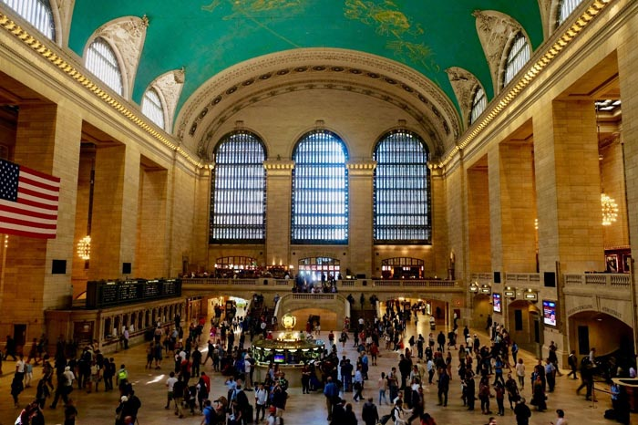 In this colour photograph taken by Ian Logan the magnificent concourse of New York's Grand Central Terminal is brightly illuminated and thronged with passengers.