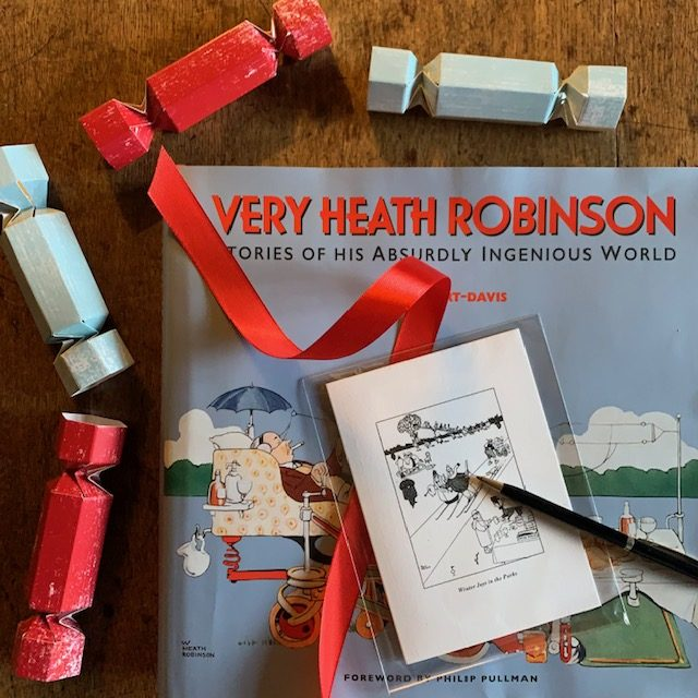 Colour photograph of a Very Heath Robinson book and a pack of six Winter Joys Christmas cards, surrounded by blue and red Christmas crackers.