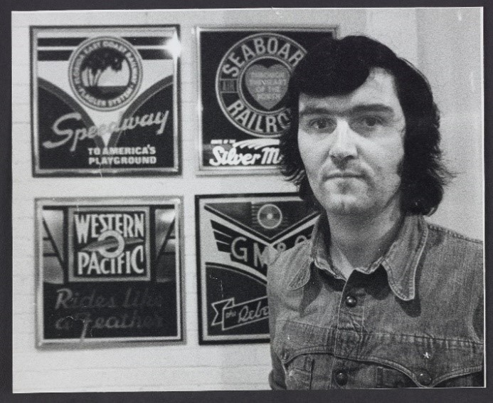 Black and white photograph of Ian Logan standing beside four American railroad logos he designed in the 1970s.