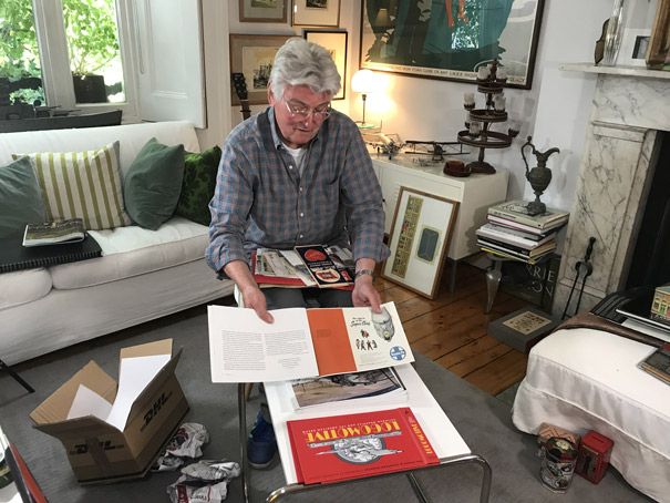 Colour photograph of a big moment when the designer Ian Logan, seated in his sitting room, sees the printed proofs of his book Logomotive for the first time.