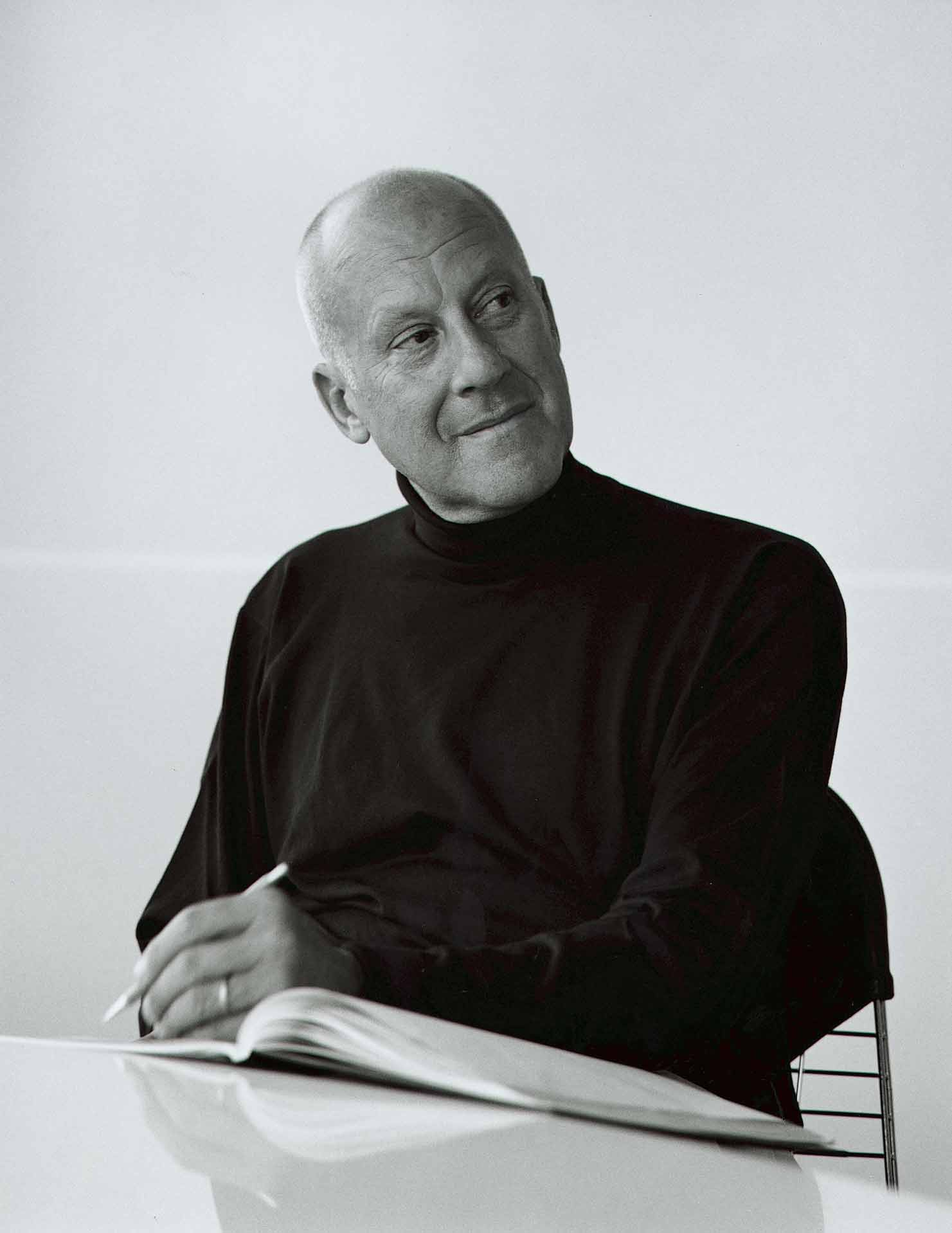 The architect Norman Foster sits with pencil and sketch book in this black-and-white portrait, courtesy of GA/Yukio Futagawa.