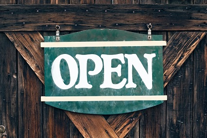 Colour photograph of an 'Open' sign. If you have time to read, we can send you a book.