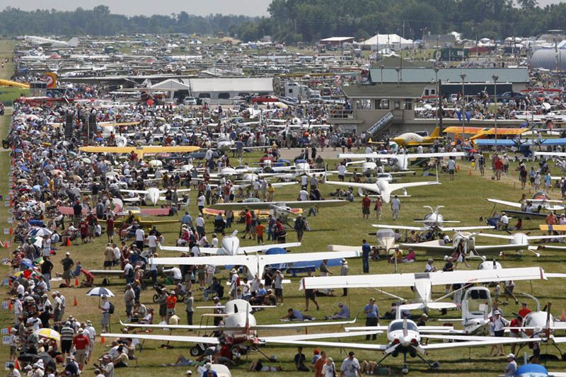 In this colour photograph visitors admire the thousands of light aircraft that have flown in for the annual EAA AirVenture show at Oshkosh, Wisconsin.