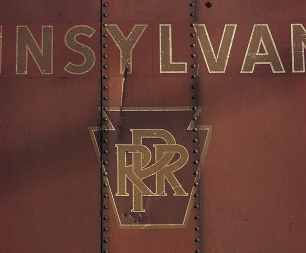 In a colour photograph taken by Ian Logan in the 1970s, the keystone logo of the Pennsylvania Railroad survives on the side of a freight wagon years after the company ceased to exist.