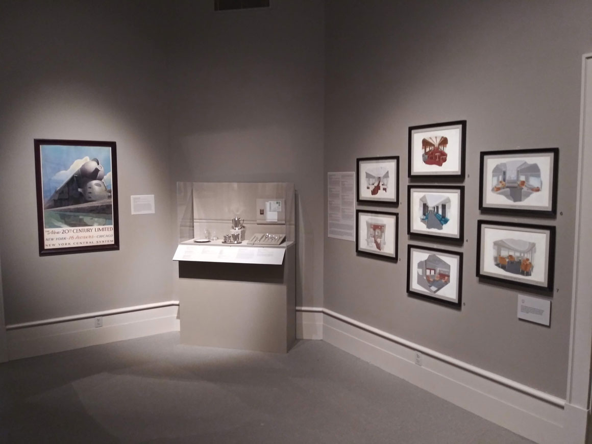 This colour photograph shows an exhibition room at the Albany Institute of History & Art featuring prints on the right-hand wall, a glass case containing silver dining-car cutlery centre and, on the far wall, a framed poster by Leslie Ragan depicting the streamlined 20th Century Limited locomotive.