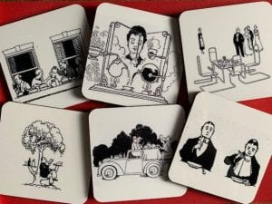 Photograph of the set of six Heath Robinson coasters, illustrated with back and white line drawings and set against a red background.
